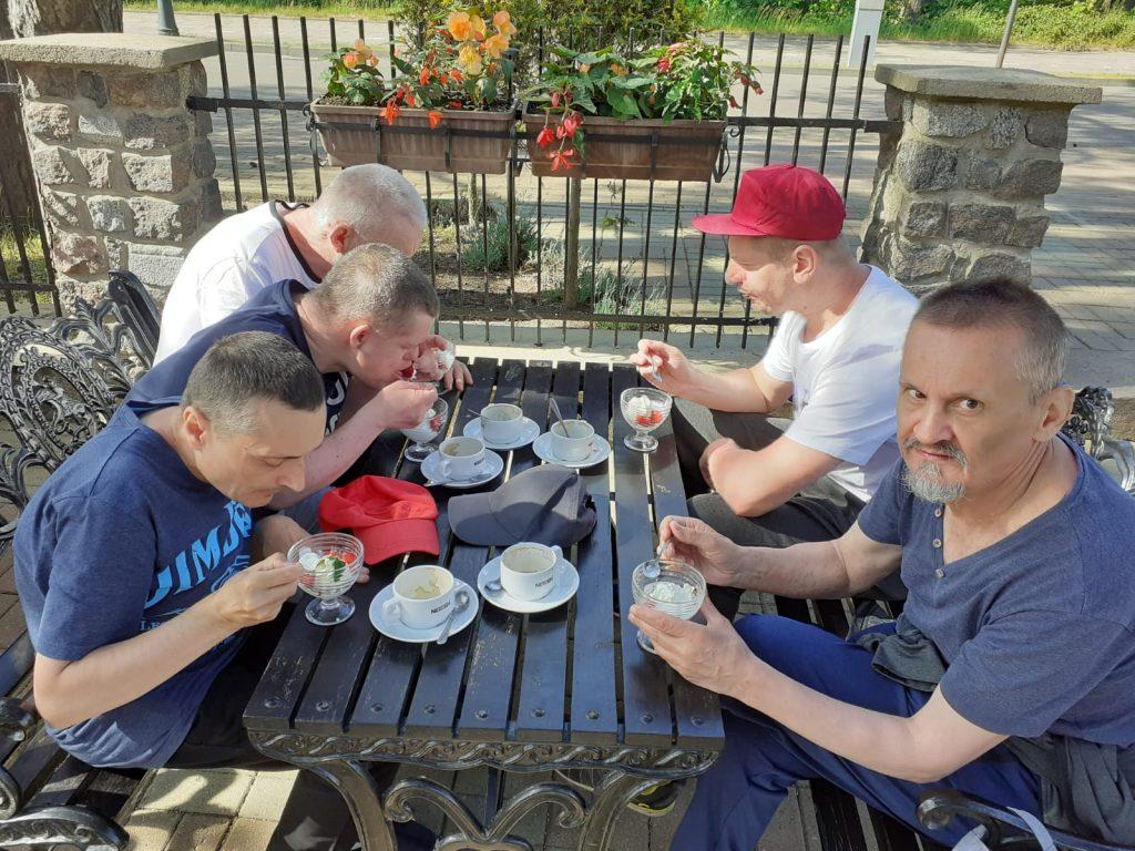 Mieszkańcy siedzący przy drewnianym stoliku na dworze spożywają deser oraz lody