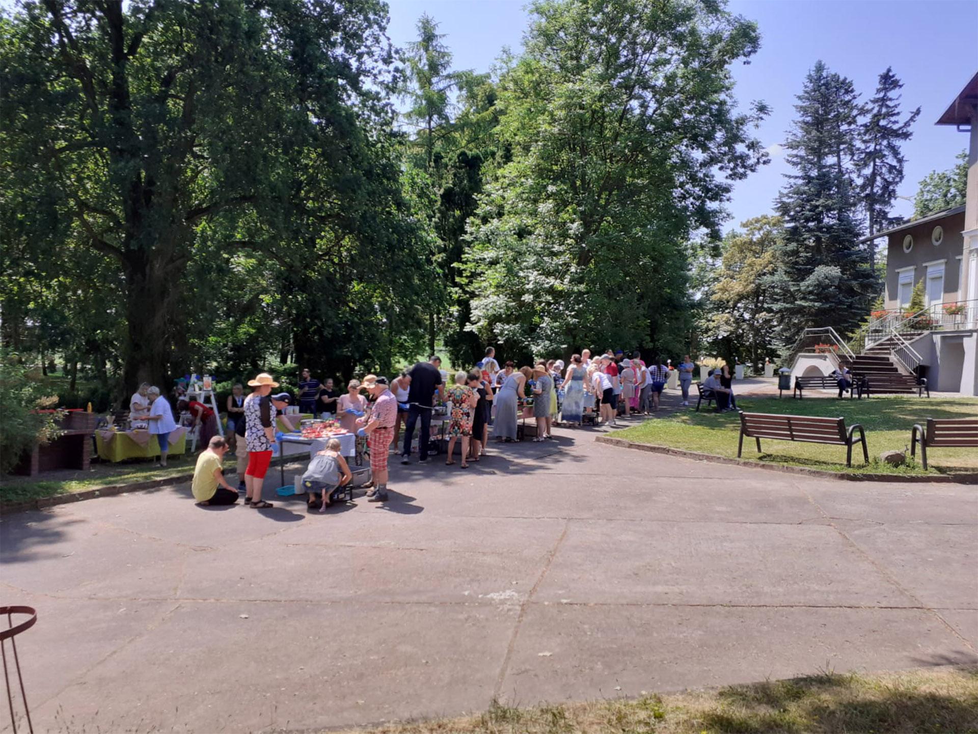 Parę stolików przy których stoją osoby robiące szaszłyki owocowe. W tle drzewa. Zdjęcie robione z oddali.
