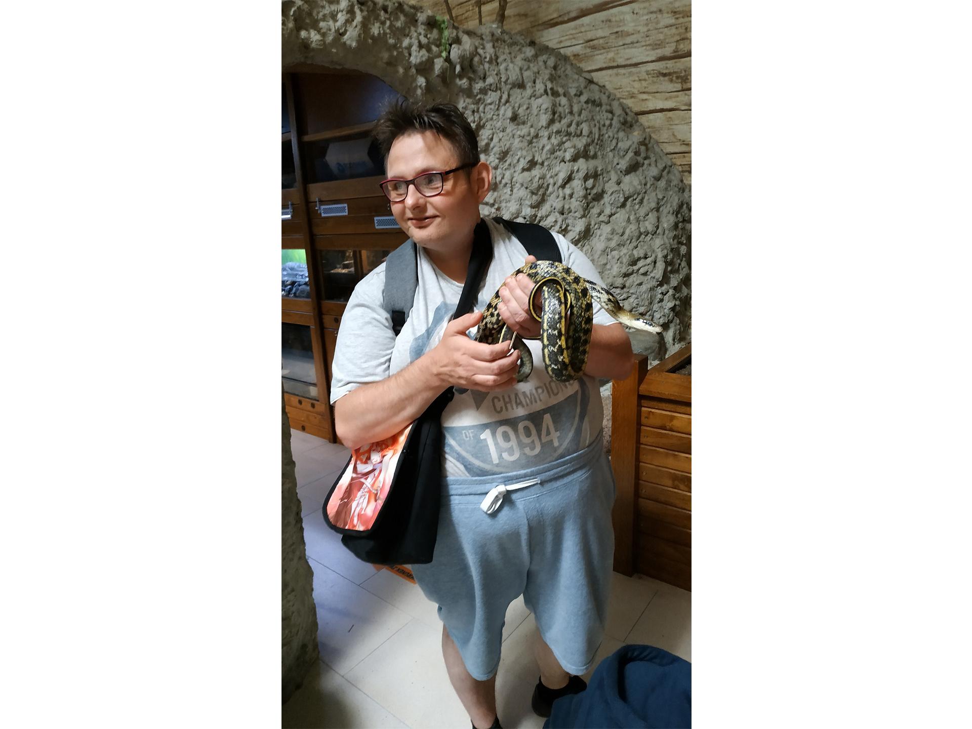 Podopieczny trzyma na rękach kolorowego węża
