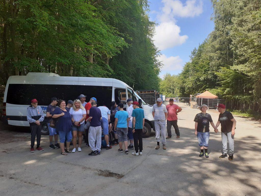 Przyjazd do Doliny Charlotty, w tle autobus, przed nim opiekuni oraz grupa osób, która wysiadła z autobusu
