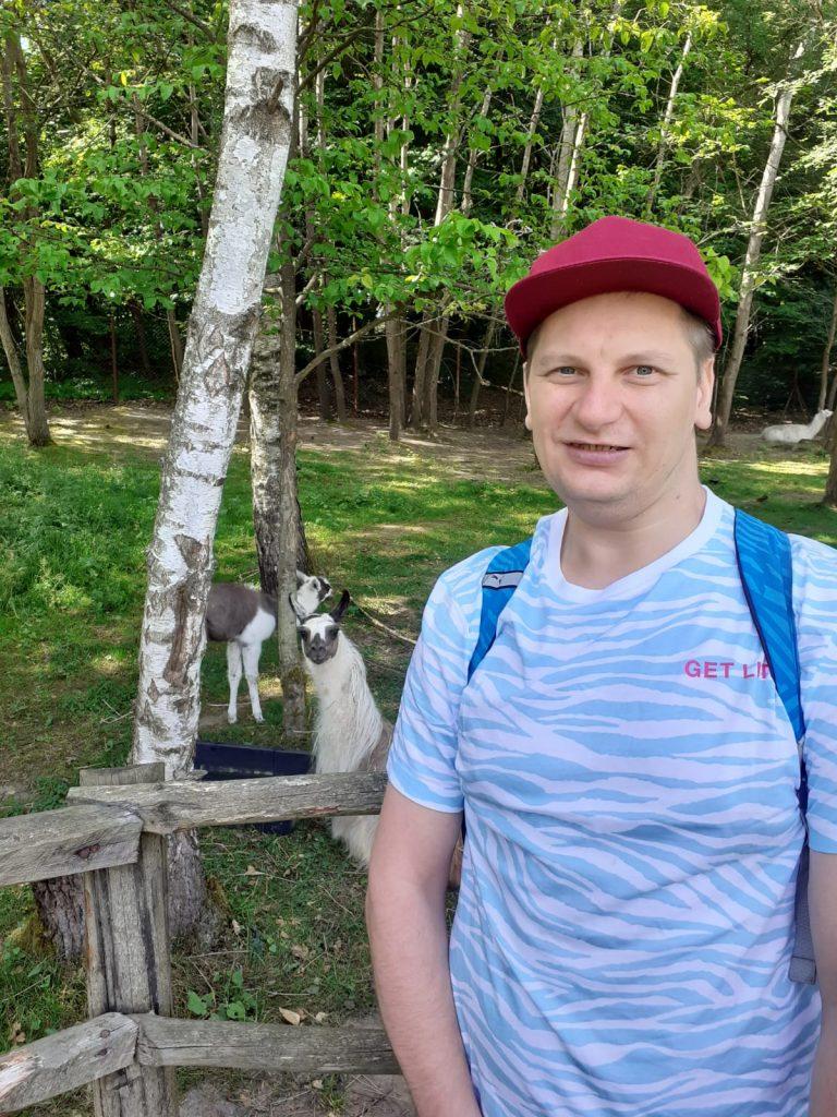 Mężczyzna ubrany w niebieską koszulkę i czerwoną czapkę na głowie lekko się uśmiecha, za nim lama