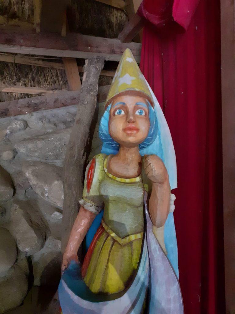 Rzeźba kobiety zrobione z drewna. Kobieta wygląda na księżniczkę, na głowie ma czapkę z długim welonem.