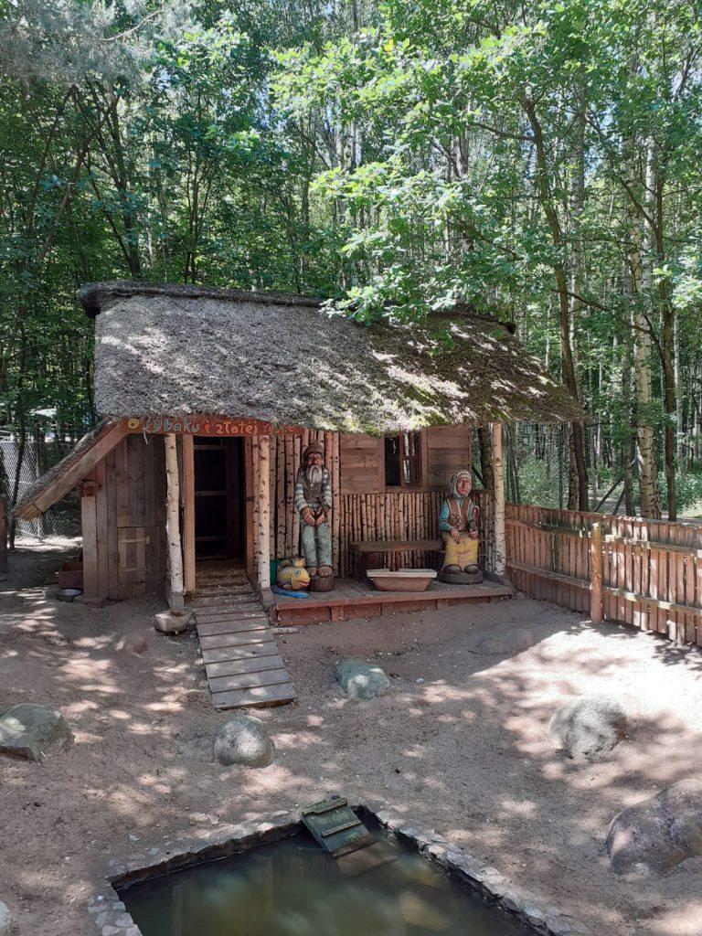 Drewniany domek, ze strzechą na dachu. Obok domku pod dachem stoją dwie rzeźby kobiety oraz mężczyzny z przed lat.