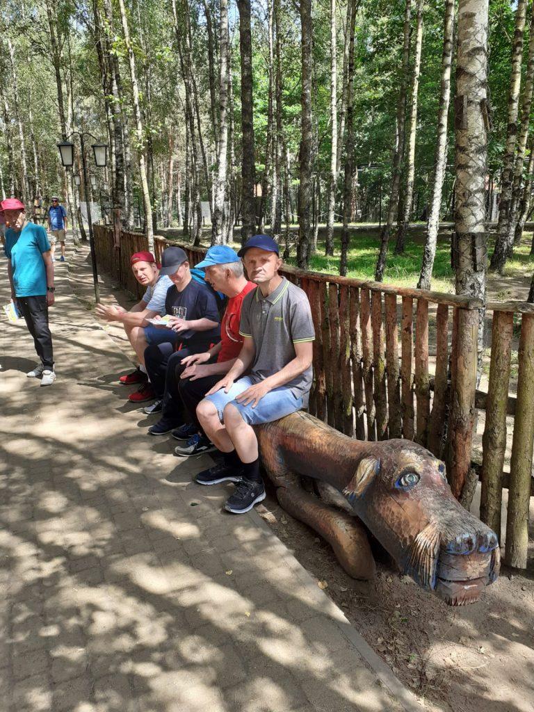 Czterech mieszkańców siedzi na drewnianej ławce, która na zakończeniu ma głowę smoka
