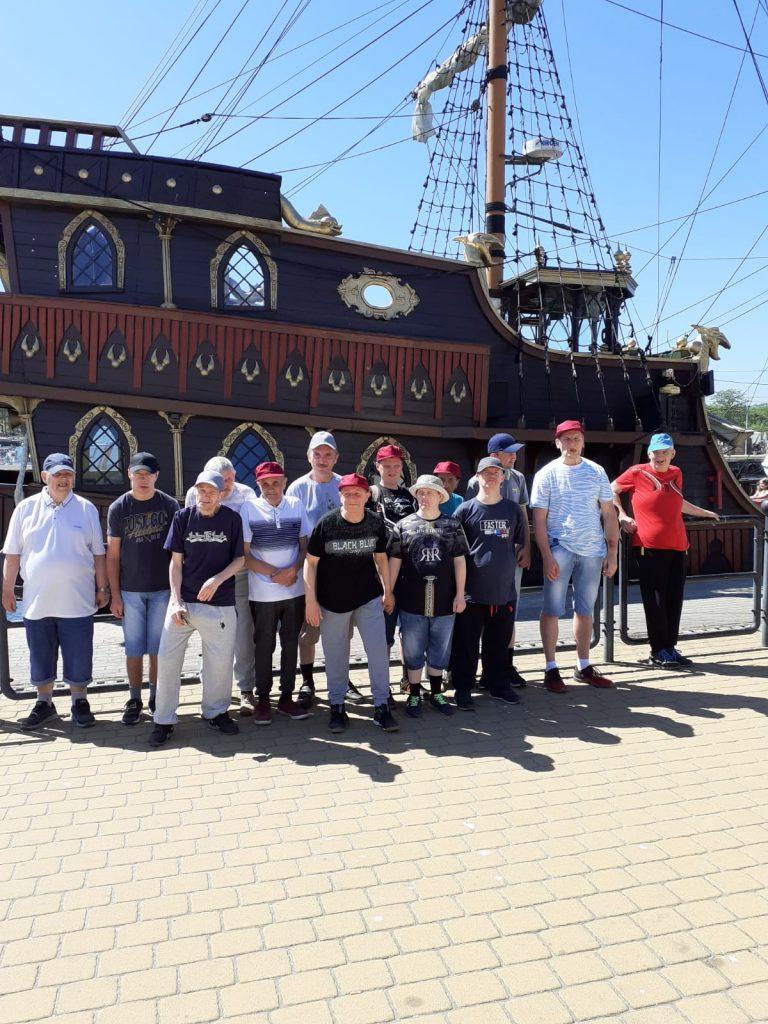 Grupa osób z wycieczki stoi przed wielkim statkiem wodnym