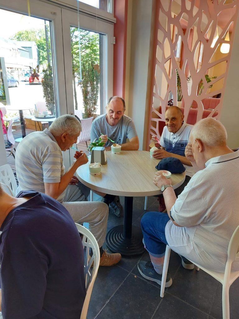 Grupa osób siedząca przy stoliku i jedząca deser