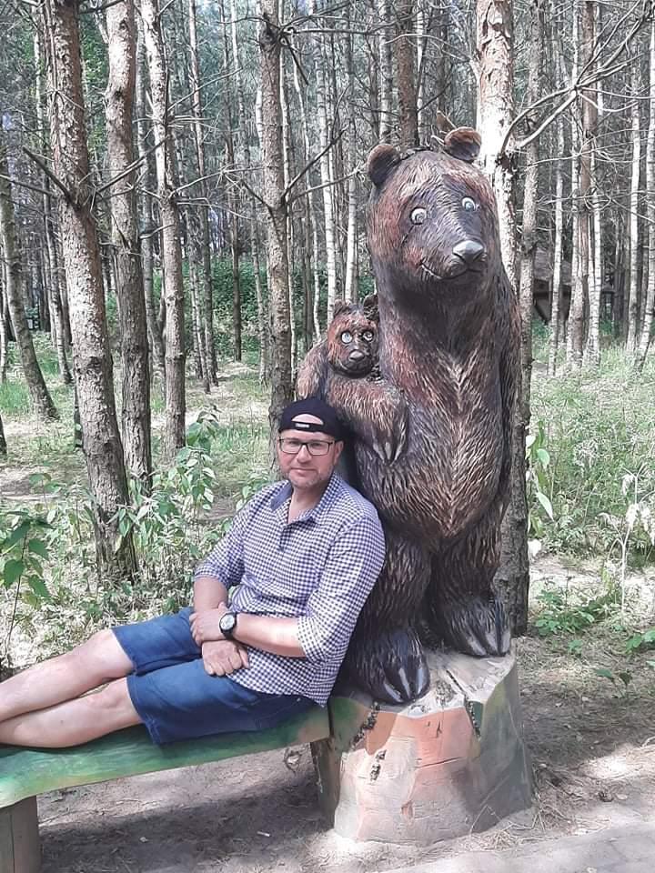 Mężczyzna w krótkich dżinsowych spodenkach i koszuli siedzi oparty o wyrzeźbionego dużego niedźwiedzia