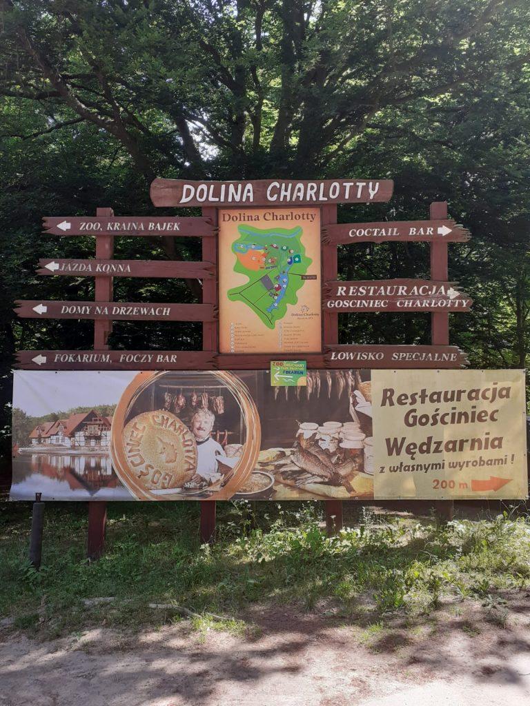 Drewniana tablica z napisem Dolina Charlotty, ukazuje małe tablice z kierunkiem na lewo oraz prawo aby dotrzeć do atrakcji