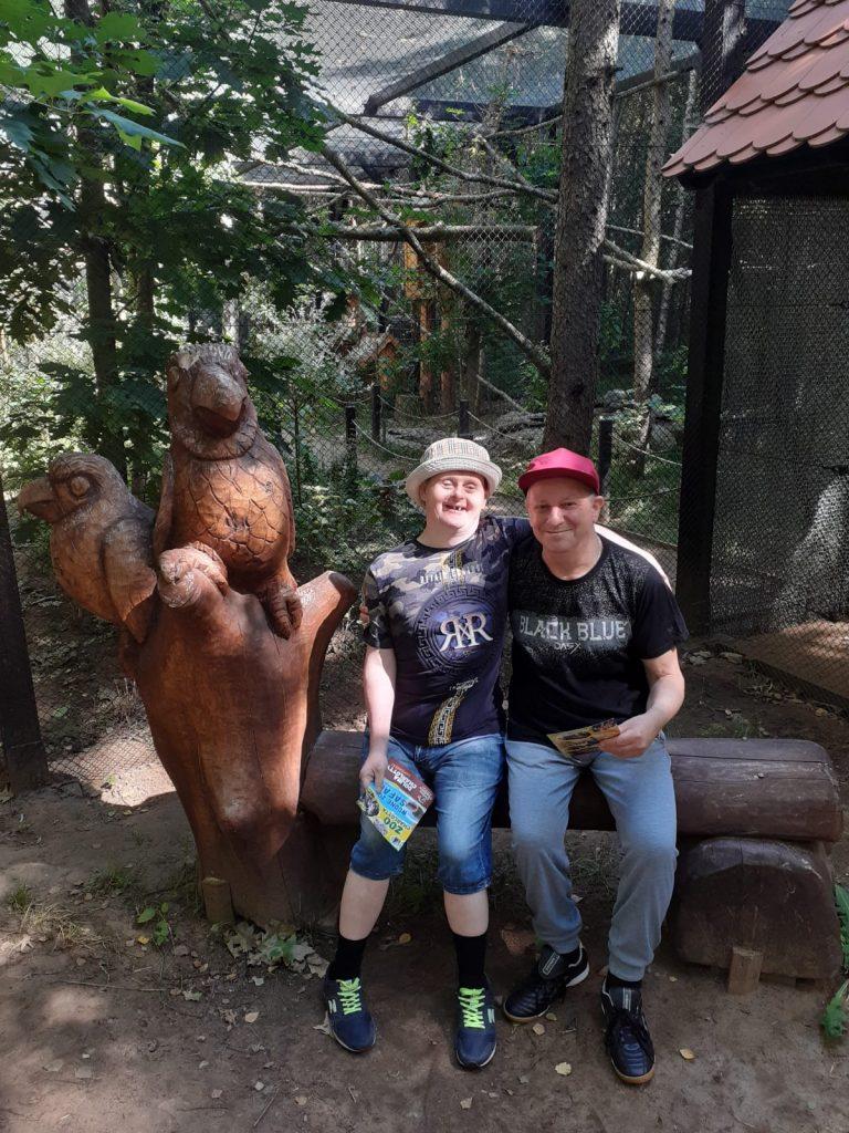 Dwóch mężczyzn uśmiechniętych siedzi na drewnianej ławce w tle klatki dla zwierząt (ptaków) obok rzeźba drewniana dwóch ptaków