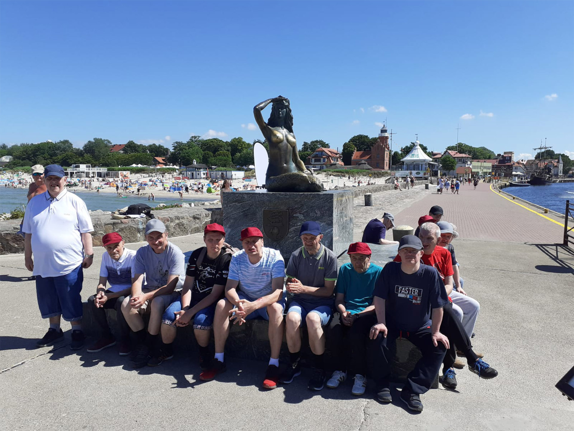 Grupa wycieczki siedzi przy pomniku kobiety z brązu, która siedzi i patrzy daleko przed siebie. Wszyscy są na promenadzie w Ustce