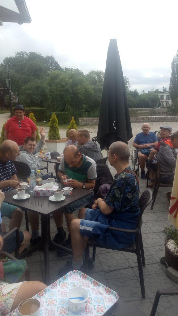 Grupa osób siedząca przy stolikach, pijąca kawę i jedząca lody.
