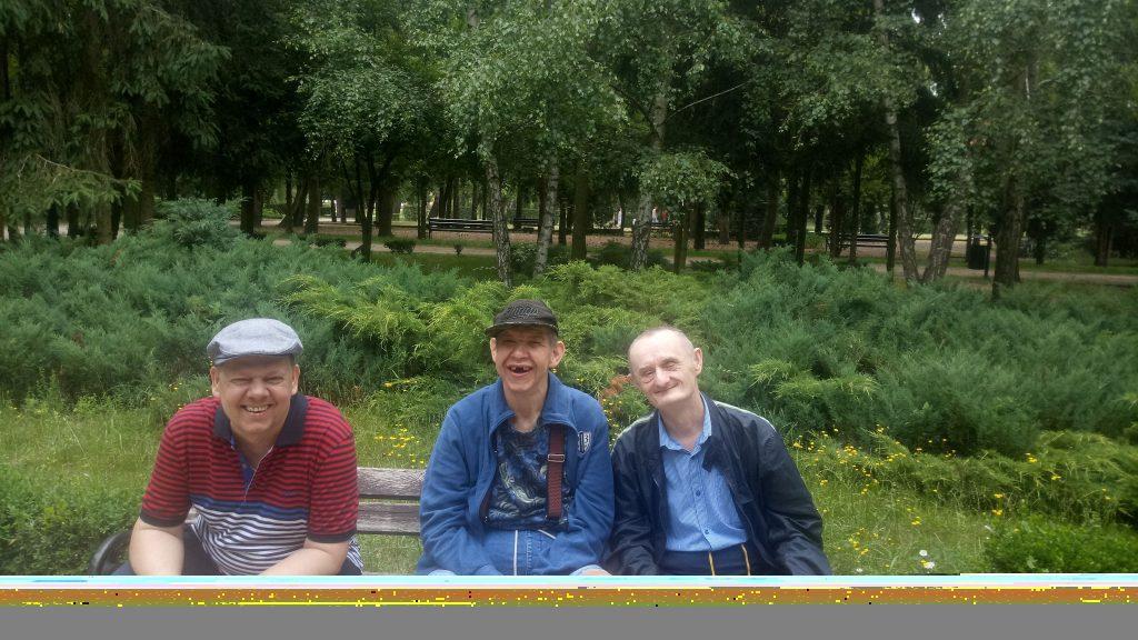 """Trzy osoby siedzące na drewnianej ławce uśmiechają się """"do zdjęcia"""""""