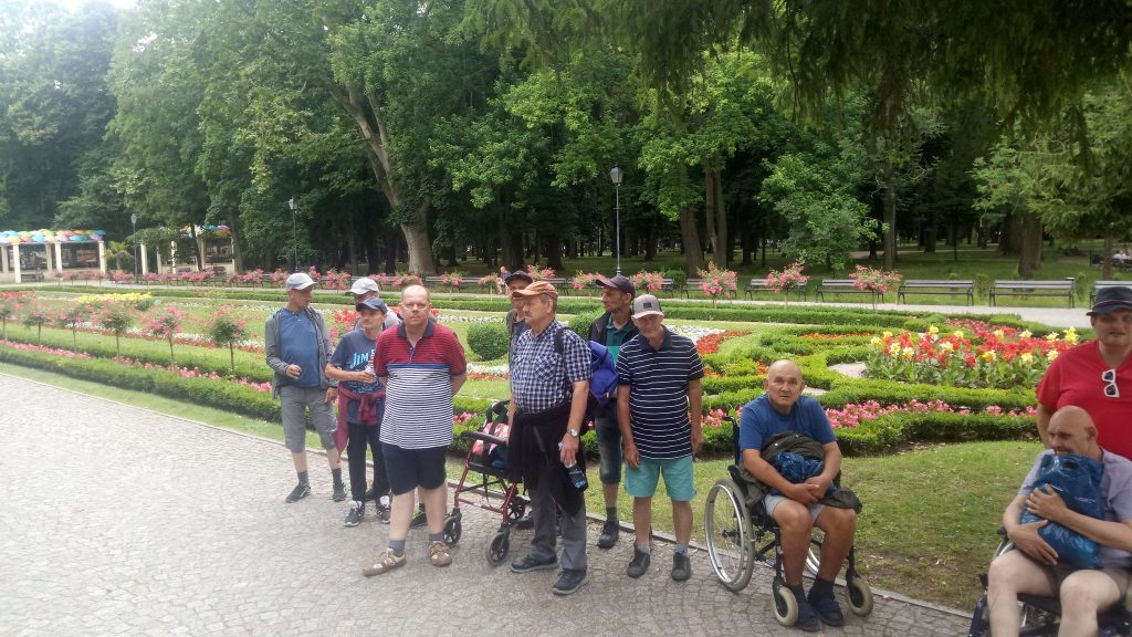Grupa osób stojąca razem, jedna osoba na wózku