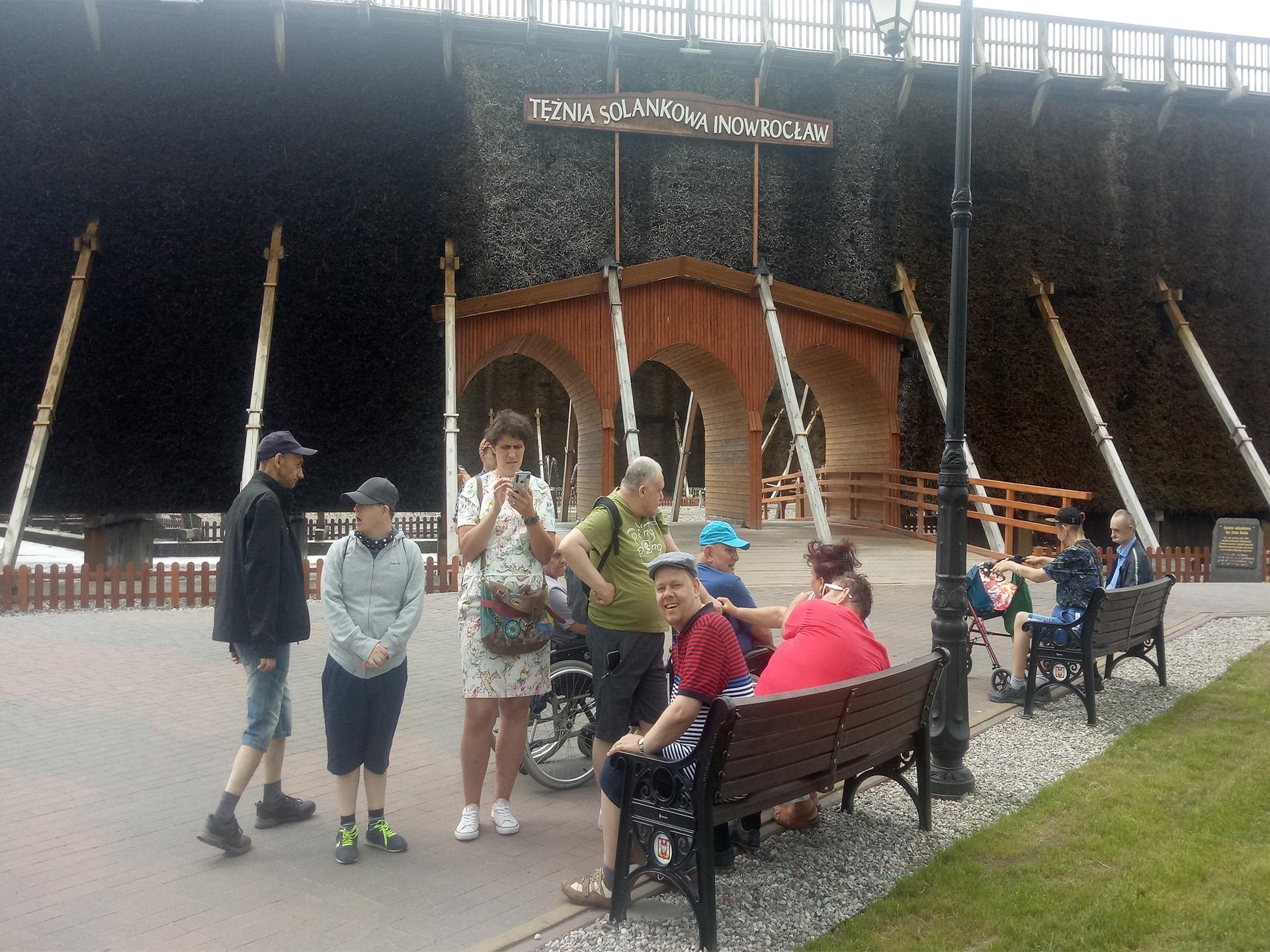 Grupa osób stojąca niedaleko wejścia do Tężni. Część osób stoi część siedzi na ławce z tyłu wejście do budynku z napisem Tężnia Solankowa Inowrocław