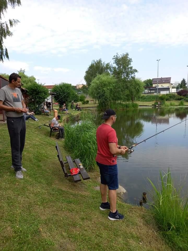 Mężczyzna w czerwonej koszulce i czarnej czapce stoi na zielonej trawie przy jeziorze z wędka w ręku zanim inny mężczyzna obserwuje.