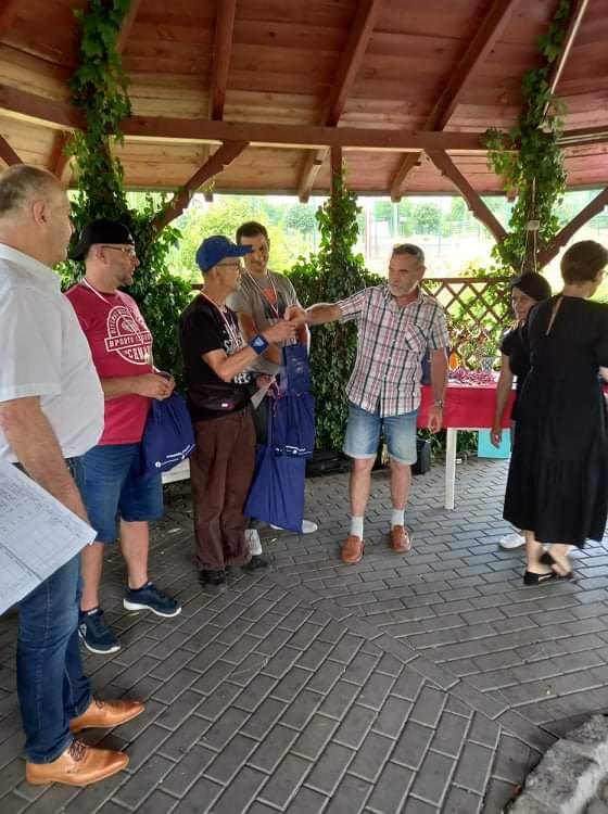 Grupa osób podczas wręczania nagród. Stoją pod drewnianą wiatą
