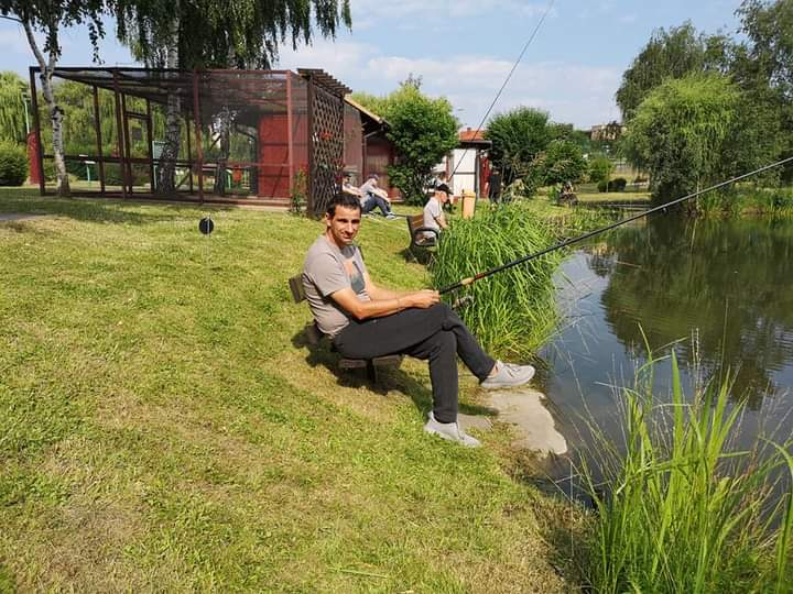 Podopieczny siedzi na zielonej trawce i trzyma wędkę zarzuconą do jeziora