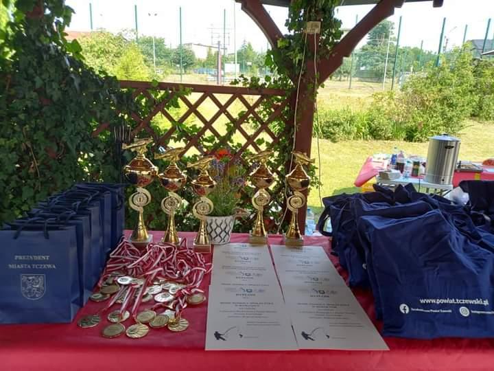 Na drewnianym stole stoją złote puchary, dyplomy oraz paczki z nagrodami