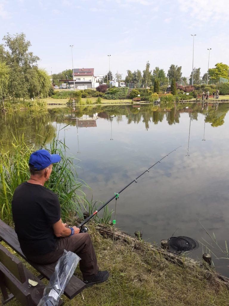 Mężczyzna w czarne koszulce i niebieskiej czapce na głowie trzyma w ręku wędkę, przed nim jezioro