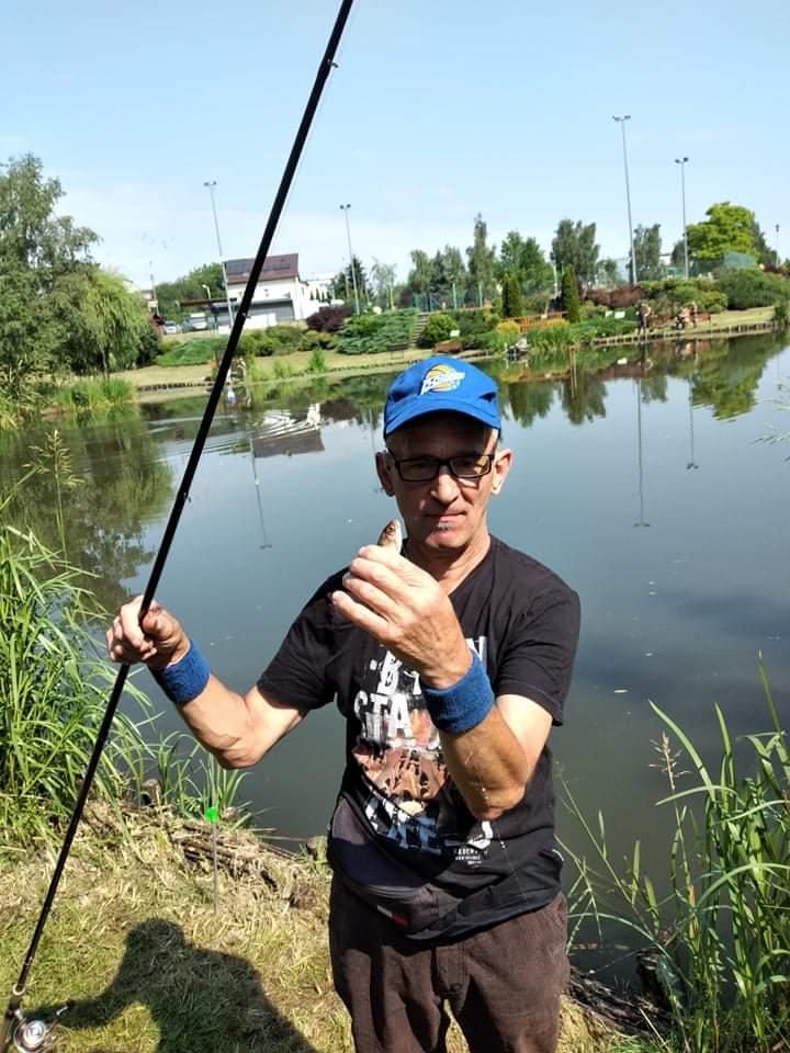Podopieczny trzyma w ręku wędkę oraz rybę. Stoi przodem do osoby robiącej zdjęcie. Za nim malownicze jezioro
