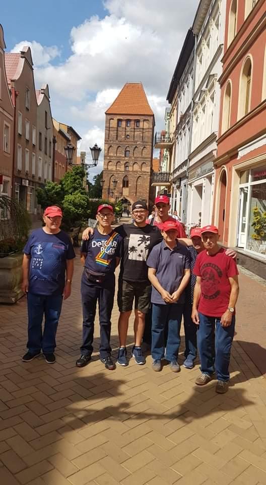 Grupowe zdjęcie podopiecznych z opiekunem w jednej z uliczek na Chojnickim rynku w tle wysoki budynek z czerwonej cegły.