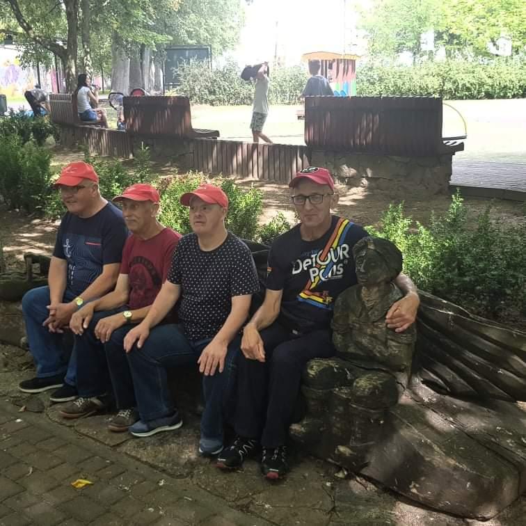 Czterech mieszkańców siedzących na ławce. Jeden z nich obejmuje drewniany posąg.