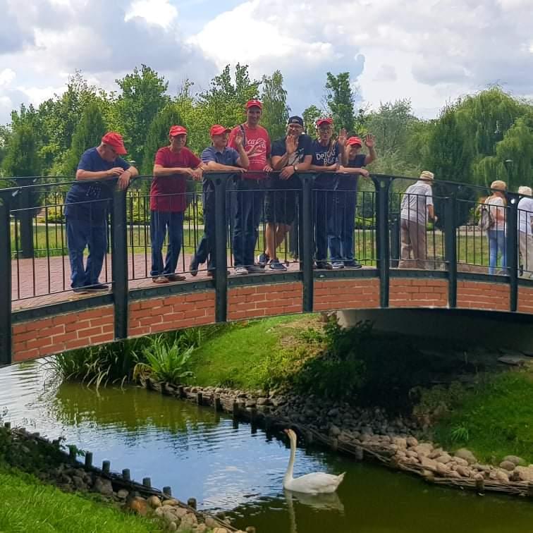 Mieszkańcy z opiekunem stoją na niewielkim moście niżej w kanale płynie biały łabędź.