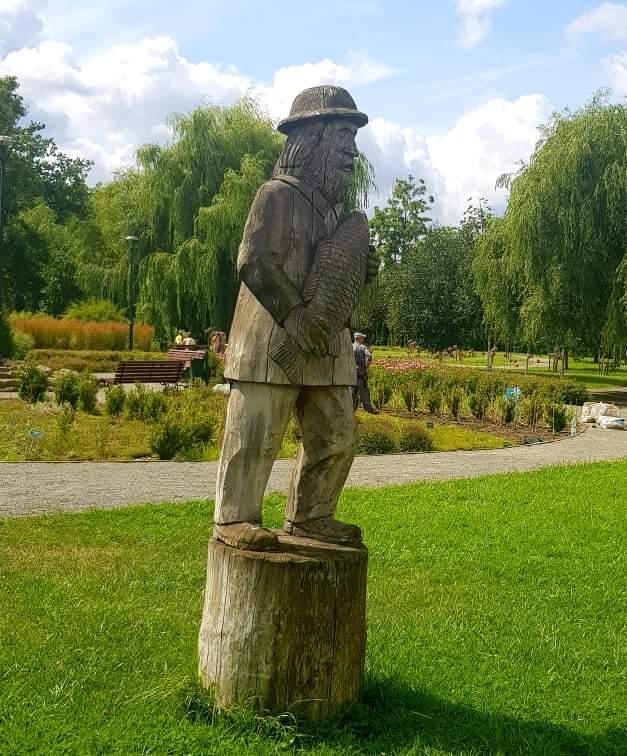 Drewniany posąg rybaka, który trzyma w ręku rybę z łuskami.