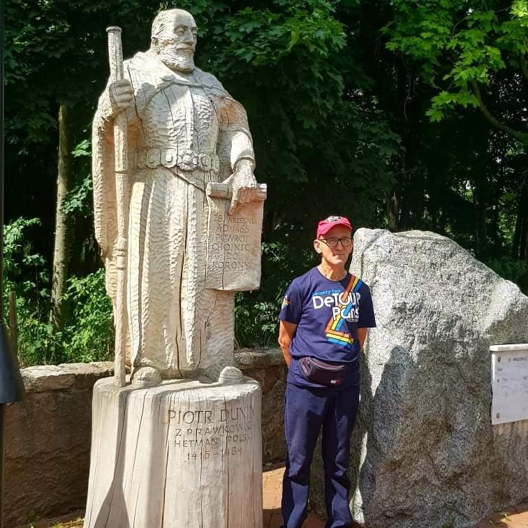 Mieszkaniec stojący przy drewnianym posągu Piotra Dunin z Prawkowic - Hetmana Polski