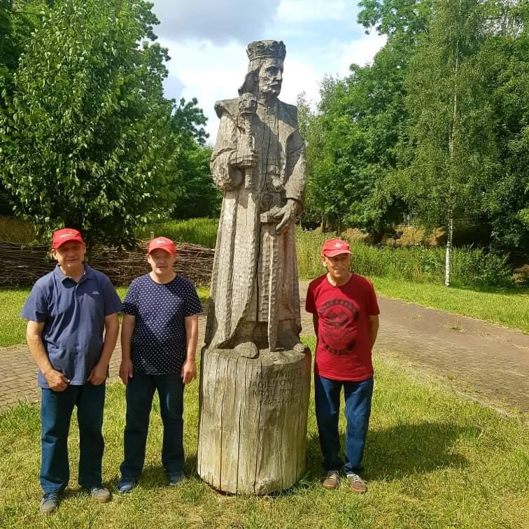 Trzech mieszkańców stoi obok drewnianego dużego posągu Króla Polski Kazimierza Jagiellończyka Króla Polski. Posąg stoi w szatach w koronie na głowie oraz w ręce trzyma miecz i berło wykonane z drewna