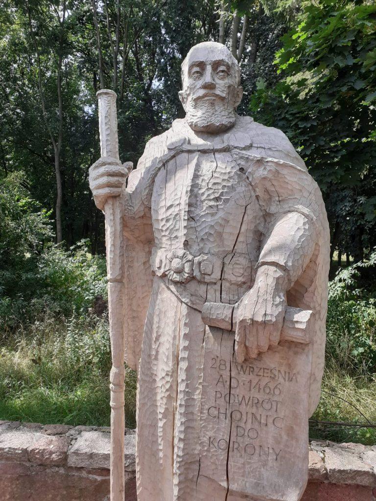 """Drewniany posąg Hetmana Polskiego trzymającego laskę oraz zwój na którym jest napisane """"28 Września A.D. 1466 Powrót Chojnic do Korony"""""""