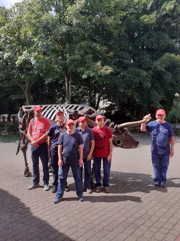 Grupa mieszkańców pod rzeźbą byka z wielkimi rogami wykonaną z metalu.