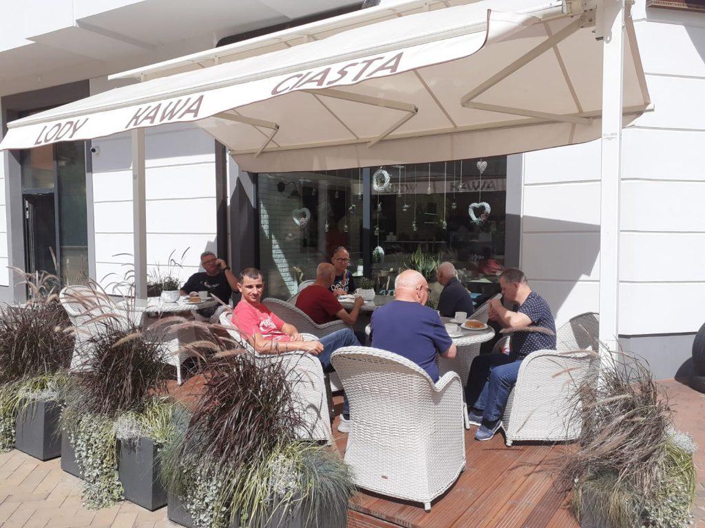 Mieszkańcy podczas spożywania lodów, ciastek i kawy, siedzą na fotelach ratanowych przy stolikach przed kawiarnią