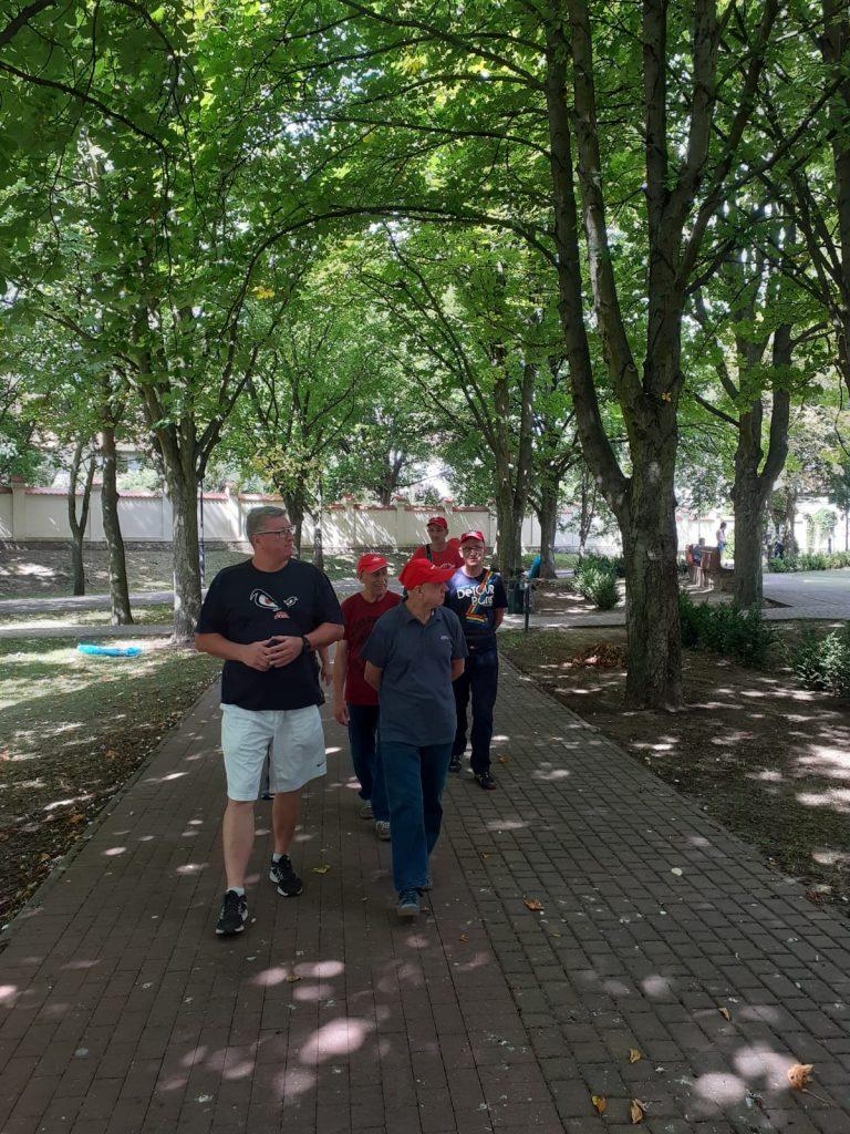 Grupa osób idących pakiem między zielonymi dużymi drzewami