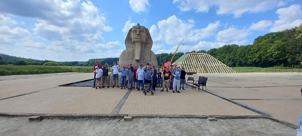 Grupa mieszkańców wraz z opiekunami pod posągiem Sfinksa