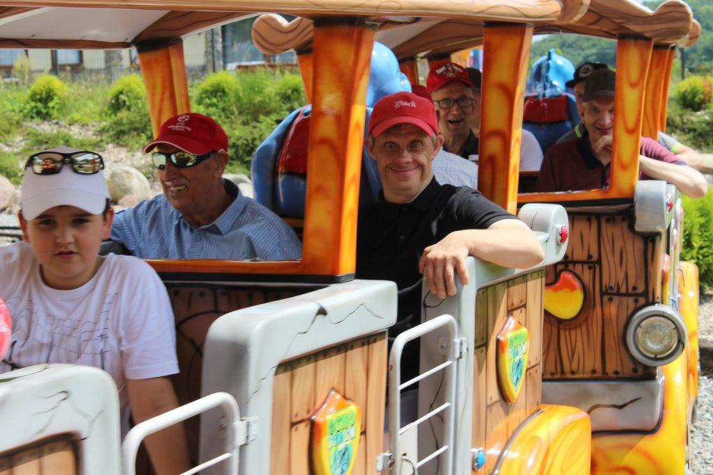 Grupa uśmiechniętych i zadowolonych mieszkańcy podczas jazdy Dino pociągiem