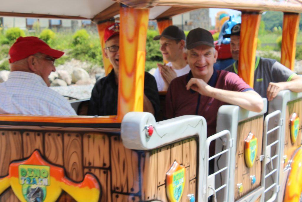 Uśmiechnięci mieszkańcy podczas jazdy Dino pociągiem
