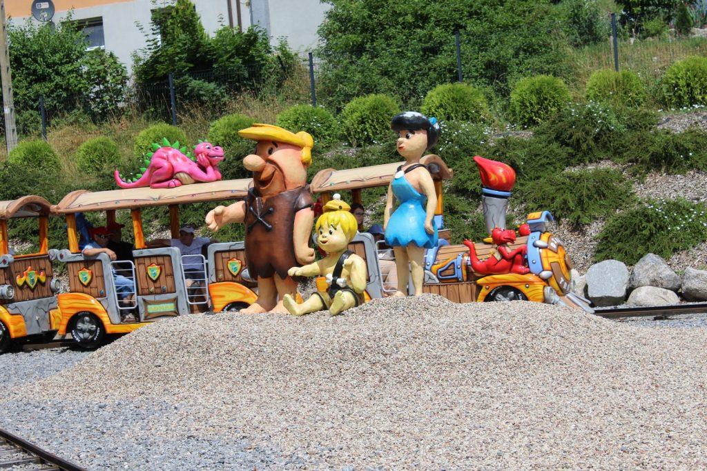 Na usypanej z kamieni niewielkiej górce stoją trzy postacie z bajki Flinstonowie, w tle jedzie kolorowy pociąg