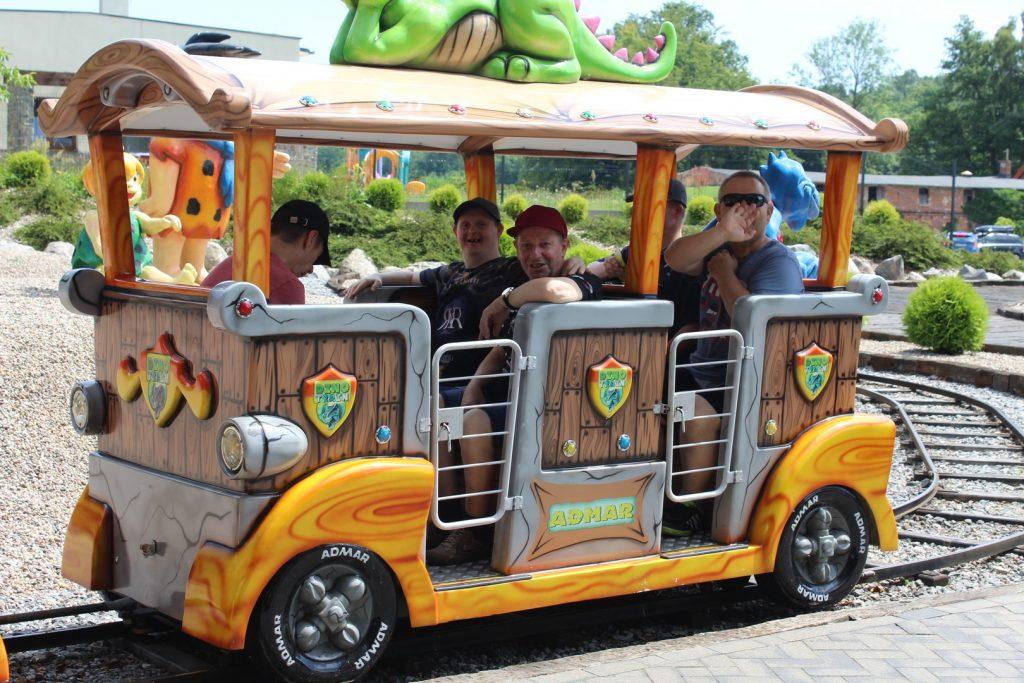 Pięciu podopiecznych siedzących w Dino pociągu jadącym po szynach. Uśmiechają się, jeden kiwa