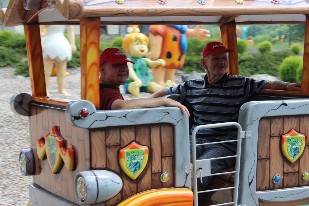 Dwóch uśmiechniętych mężczyzn siedząca w kolorowym Dino pociągu.