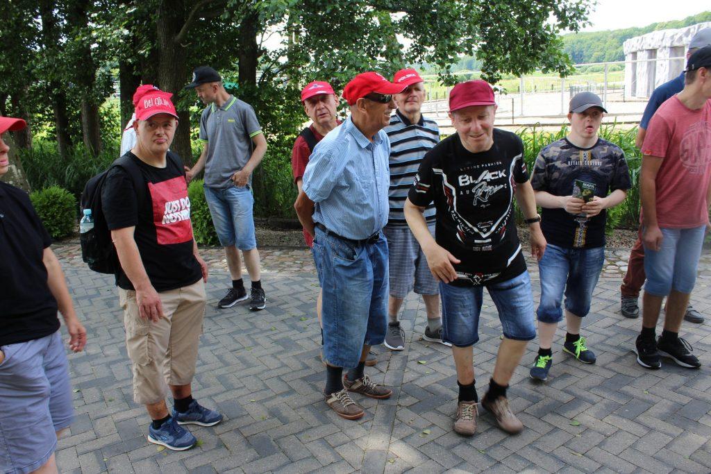 Grupa osób stojących obok siebie, na głowach mają czapki za nimi zielone drzewa oraz ogrodzony budynek
