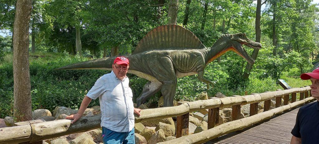 Mężczyzna w czerwonej czapce, koszuli w kratę i okularach oparty o drewniany niski płotek w tle las oraz postać dinozaura