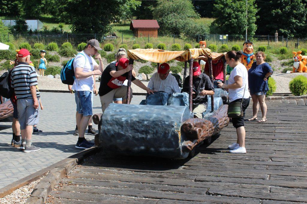 Grupa osób, która wsiada do pojazdu Flinstonów, dach jest z materiału obok imitacja drewna, a z przodu walec. Część siedzi, jedna wsiada.