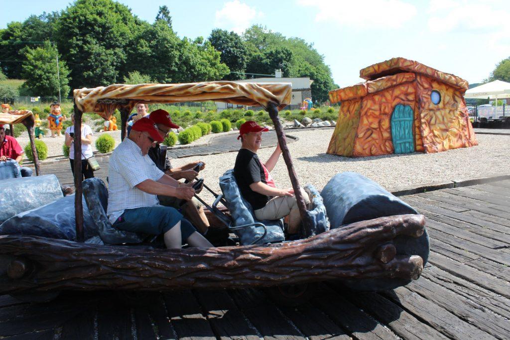 Trzech mieszkańców siedzących w pojeździe Flinstona. Dwóch z nich kieruje pojazdem