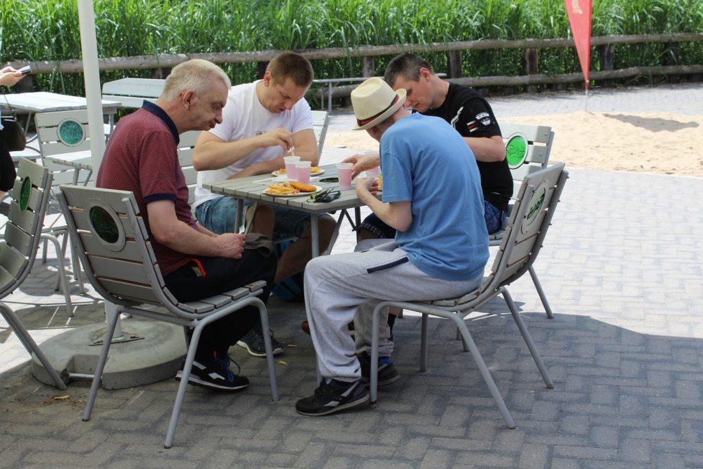 Mieszkańcy podczas konsumpcji jedzenia w Parku Ewolucji siedzą w cieniu przy drewnianym stoliku