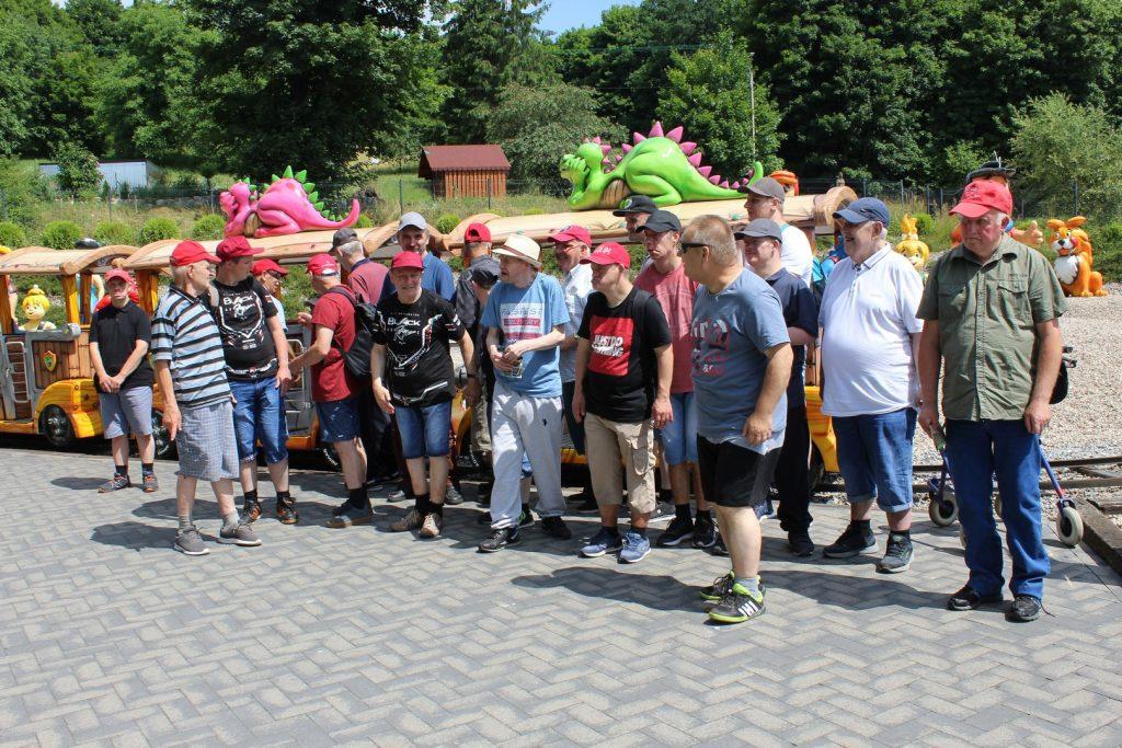 Grupa wycieczkowa stojąca obok Dino pociągu