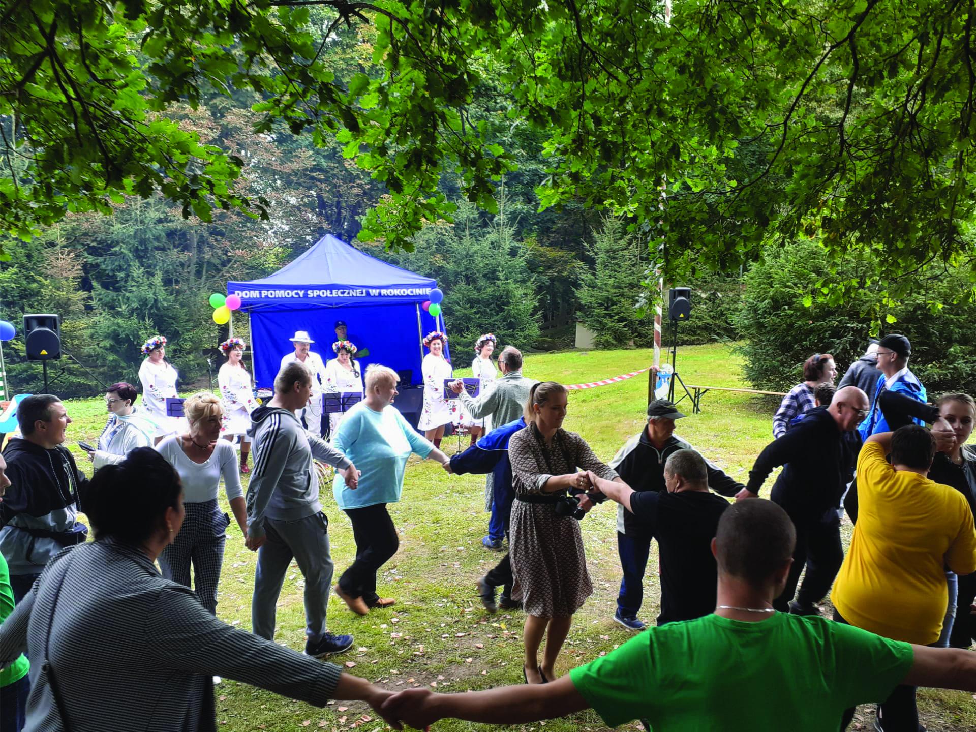 Grupa osób tańczy razem trzymając się za ręce w tle zespół folkowy