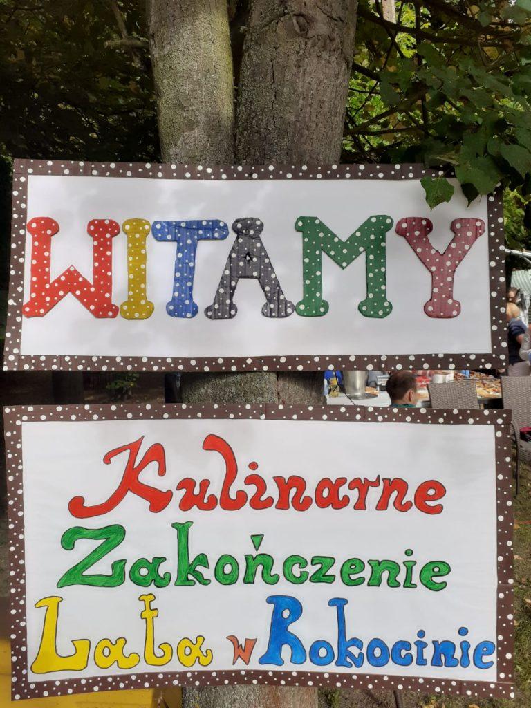 """Kolorowe dwie tablice z napisami """"Witamy"""" oraz """"Kulinarne Zakończenie Lata w Rokocinie"""""""