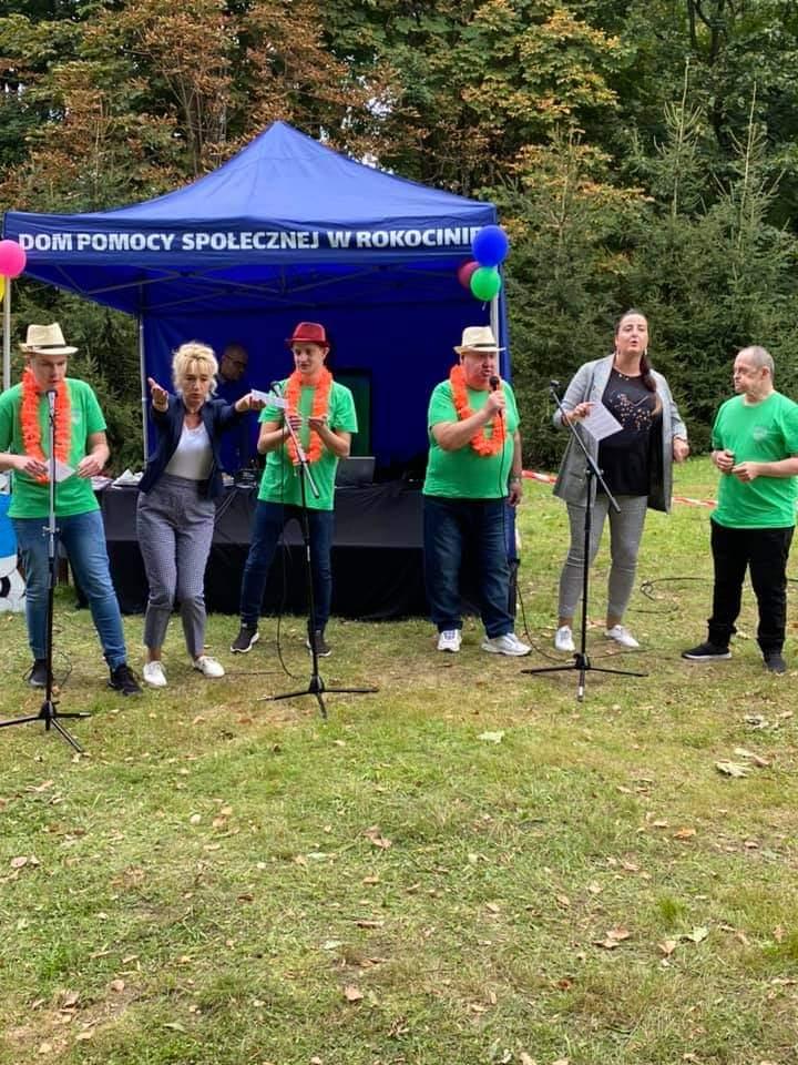 Podopieczni ubrani w zielone koszulki wraz z opiekunami stoją przed mikrofonami i razem śpiewają
