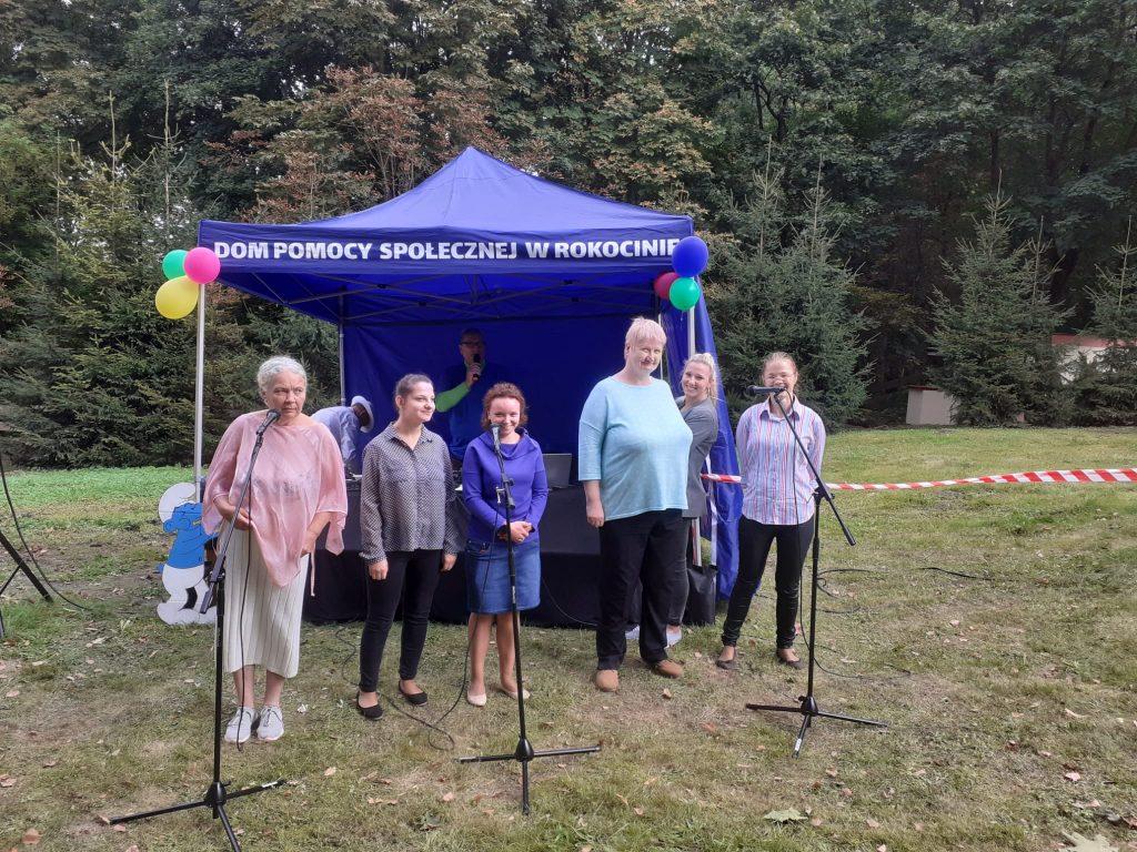 Sześć kobiet stoi przed niebieskim namiotem z napisem Dom Pomocy Społecznej w Rokocinie, a przed nimi trzy mikrofony na metalowych statywach